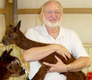 John Arnold holding 1 day old Alpaca Baby